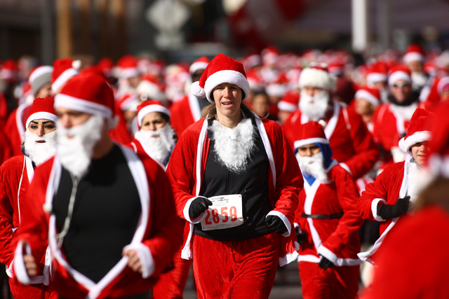 People head out from the start line down Fremont Street during the Great Santa Run in downtown Las Vegas on Saturday, Dec. 7, 2013. Over 11,000 people participated in the 5k run and 1 mile walk. ( ...