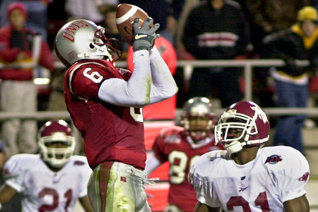 UNLV wide receiver Nate Turner makes a touchdown reception to tie the game at 14-14 as Arkansas' Orlando Green looks on during the second quarter of the Las Vegas Bowl Thursday, Dec. 21, 2000, in  ...