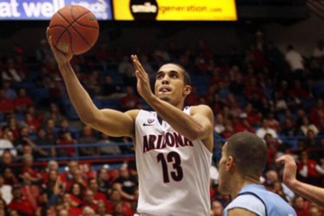 Arizona's Nick Johnson lays the ball up over Rhode Island's Jarelle Reischel in a game on Nov. 19 in Tucson, Ariz.  (AP Photo/Wily Low)