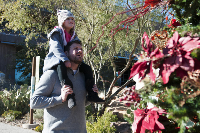 Drew Gregory carries his daughter Maya, 5, on his shoulders during a family visit to Springs Preserve in Las Vegas on Saturday. The Springs Preserve is offering activities for children during the  ...