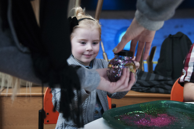 Ashley Blair, left, helps her daughter Scarlett, 4, to add the finishing touches to her snow globe during a children's activity session at Springs Preserve in Las Vegas on Saturday. The Springs Pr ...