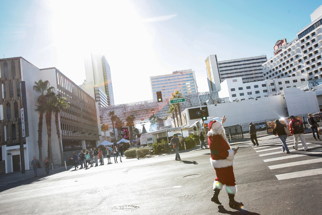 Glenn Rodgers as Santa Claus waves to people walking nearby the Jingle Bell Block event on Third Street between Stewart and Ogden avenues on Saturday. The event, held by Downtown Grand Las Vegas a ...