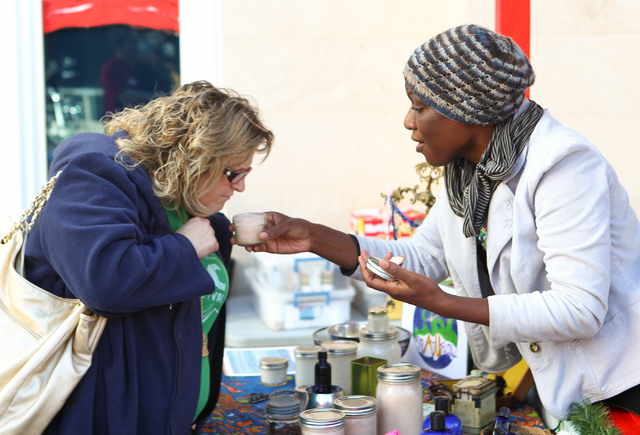 Ikeda Thompson of Au Natural 360, right, shows her products to Jennifer St. Antoine of Escondido, Calif., at the Jingle Bell Block event on Third Street between Stewart and Ogden avenues. The even ...
