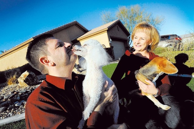 Nevada State Sen. Mark Manendo, left, gets a kiss from one of his dogs, Coco, as Robin Reddle holds Carson near their Las Vegas home on Sunday. (David Becker/Las Vegas Review-Journal)