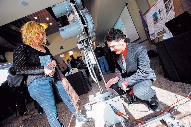 Robert Callahan, right, of the Automated Sports Ball Launcher project, shoes the device to his mom, Lisa Marhevka, during the Senior Design Competition at the Foundations Building at the Universit ...