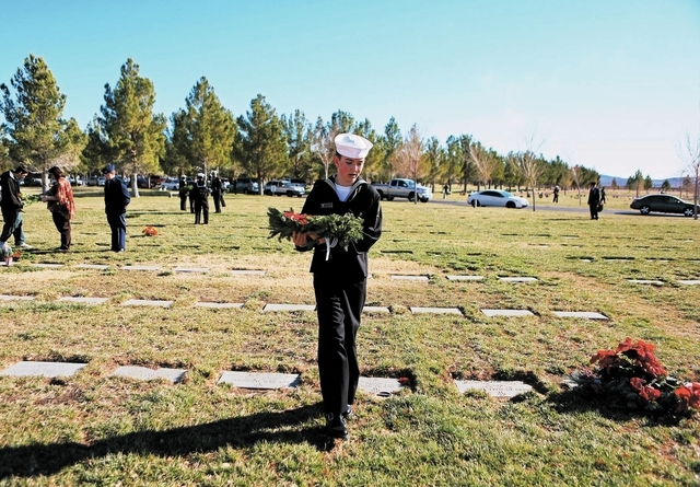 U.S. Naval Sea Cadet Corps member Beau Fairless looks for a the grave of a fallen soldier during a Wreaths Across America event at Veterans Memorial Cemetery Saturday, Dec. 14, 2013, in Boulder Ci ...
