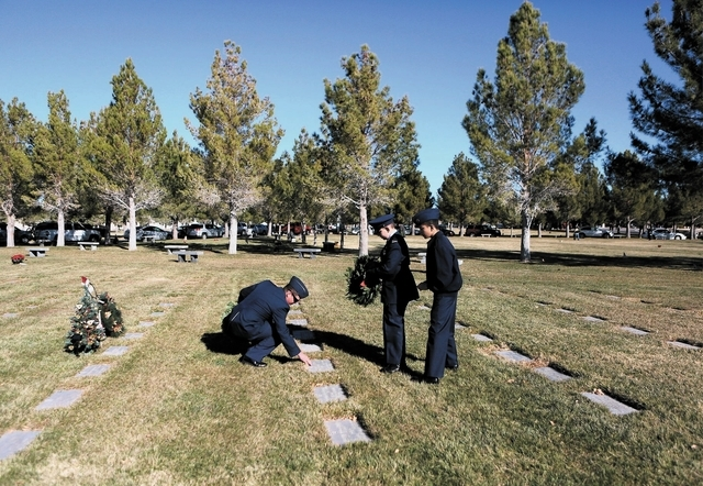 U.S. Air Force Senior Airman Cory Setera, left, bends down to wipe debris off of the grave of Staff Sgt. Michael Lopez Townes during a Wreaths Across America event at Veterans Memorial Cemetery Sa ...