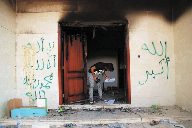 In this Wednesday, Sept. 12, 2012, file photo, a man looks at documents at the U.S. consulate in Benghazi, Libya, after an attack that killed four Americans, including Ambassador Chris Stevens. (A ...
