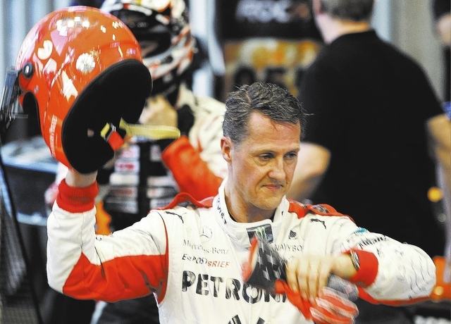 Michael Schumacher holds his helmet after a test drive at Rajamangala National Stadium in Bangkok on Dec. 16, 2012. Doctors offered no insight Tuesday into the prognosis of the seven-time Formula  ...