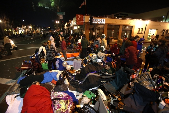 Bundled in blankets, people wait on the street in the early-morning cold before the start of the Tournament of Roses Parade in Pasadena, Calif., Wednesday, Jan. 1, 2014. (AP Photo/Ringo H.W. Chiu)