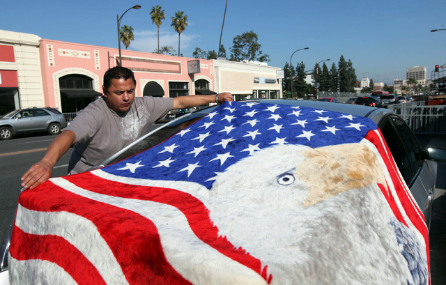 Tim Teran spreads a blanket at his spot on Colorado Boulevard as he prepares for the Rose Parade Tuesday, Dec. 31, 2013 in Pasadena, Calif.  Teran says he's been attending the parade for 33 years, ...