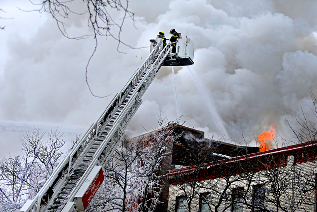 Firefighters work the scene where a fire engulfed several apartment units in the Cedar Riverside neighborhood, in Minneapolis, Wednesday, Jan. 1, 2014. Authorities say at least 13 people have been ...