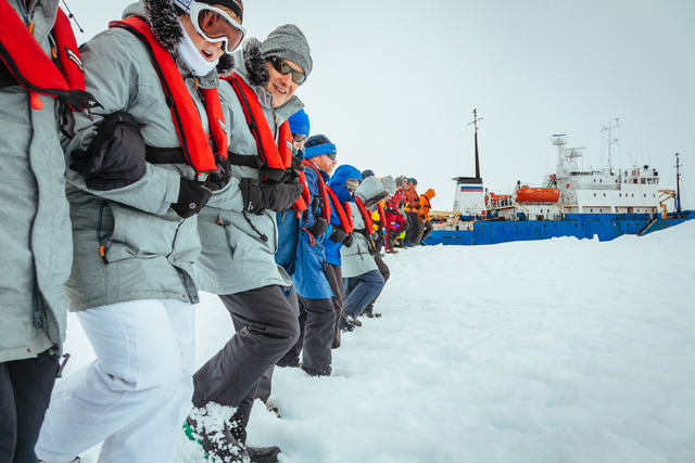 Passengers from the Russian ship MV Akademik Shokalskiy on Tuesday link arms and stamp out a helicopter landing site on the ice near the trapped ship 1,500 nautical miles south of Hobart, Australi ...
