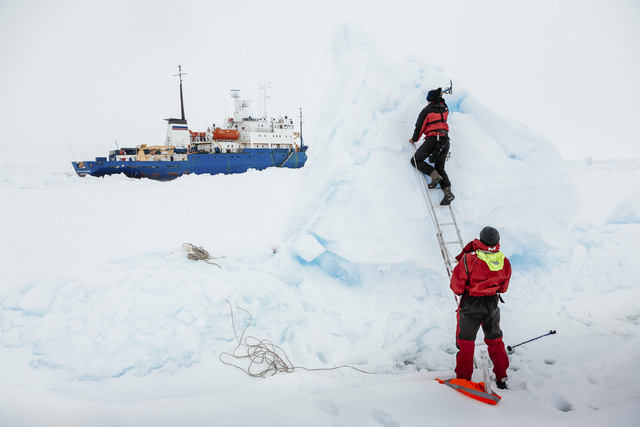 Ben Maddison and Ben Fisk from the Russian ship MV Akademik Shokalskiy work Tuesday to place a wind indicator atop an ice feature near the trapped ship 1,500 nautical miles south of Hobart, Austra ...