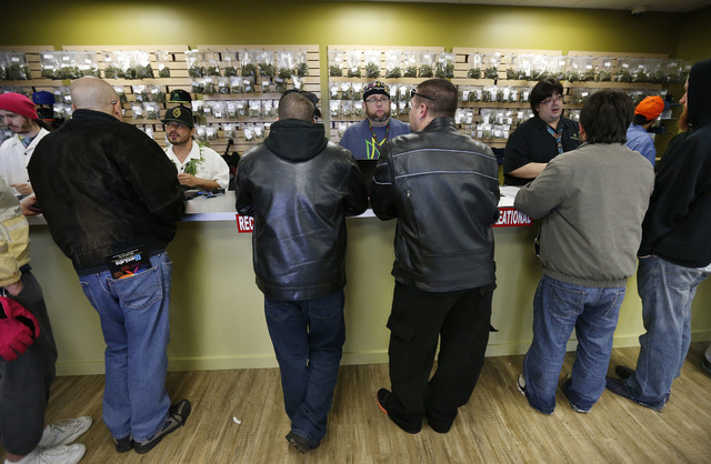Employees help customers at the crowded sales counter inside Medicine Man marijuana retail store, which opened as a legal recreational retail outlet in Denver on Wednesday Jan. 1, 2014. Colorado b ...