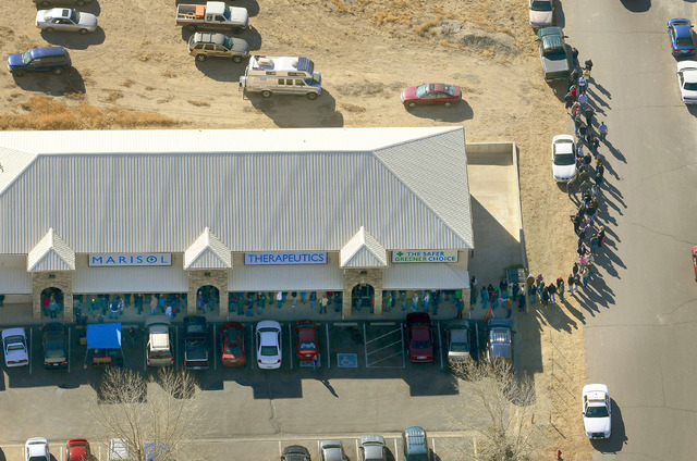 A long line of buyers trails from a store selling marijuana in Pueblo West, Colo, Wednesday, Jan. 1, 2014. The nation's first recreational pot industry opened in Colorado on Wednesday, kicking off ...