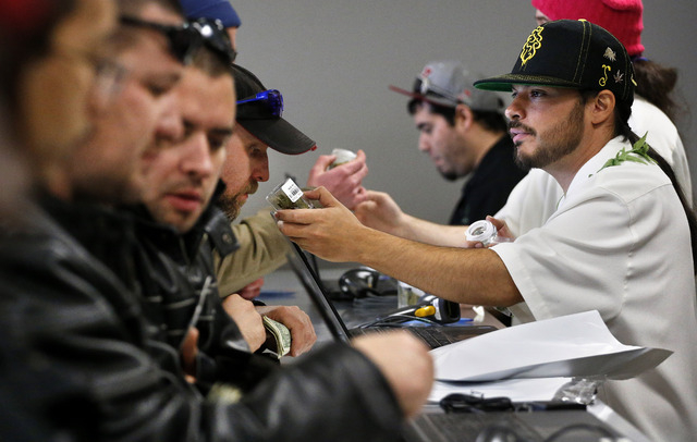 Employee David Marlow, right, helps a customer, who smells a strain of marijuana before buying it, at the crowded sales counter inside Medicine Man marijuana retail store, which opened as a legal  ...