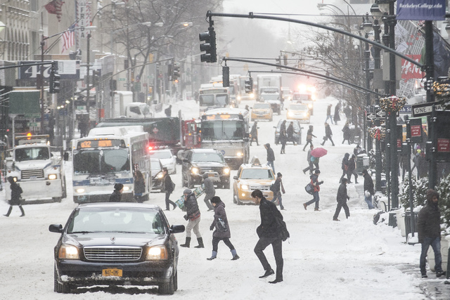 Pedestrians brave wind and snow as they cross Fifth Avenue, Friday, Jan. 3, 2014, in New York. New York City public schools were closed Friday after up to 7 inches of snow fell by morning in the f ...