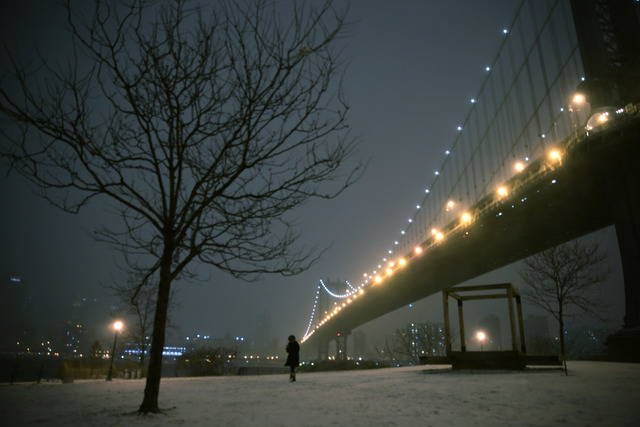 A woman walks through a park on the waterfront in Brooklyn near the Manhattan Bridge during a winter storm in New York, Thursday, Jan. 2, 2014. The storm is expected to bring snow, stiff winds and ...