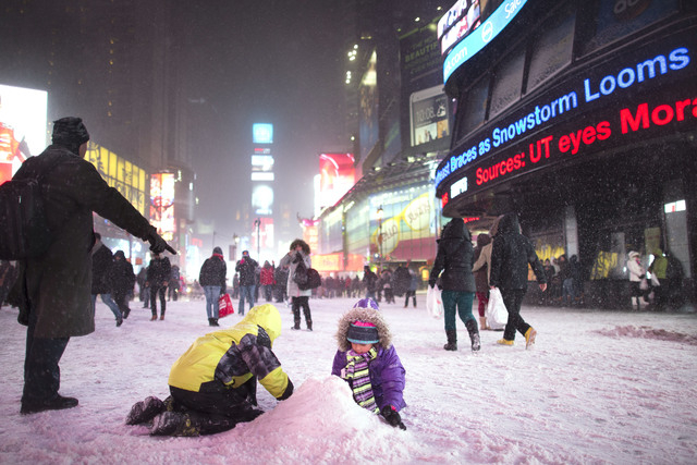 Children make a snow pile in Times Square, during a snowstorm, Thursday, Jan. 2, 2014, in New York. The storm is expected to bring snow, stiff winds and punishing cold into the Northeast. (AP Phot ...