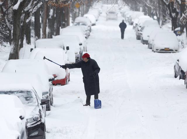 A man clears snow from a vehicle on Friday, Jan. 3, 2014, in Albany, N.Y.  A winter storm slammed into the U.S. Northeast with howling winds and frigid cold, dumping nearly two feet (60 centimeter ...