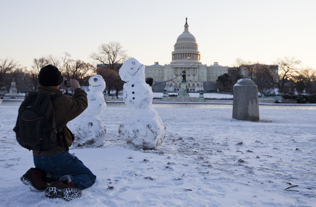 A man takes photos of snowmen with the Capitol in the background, Friday, Jan. 3, 2014, in Washington. After a storm blew through the Washington region overnight, roads are being cleared and many  ...