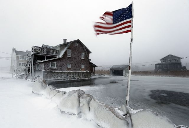 A tattered flag flies by a flooded yard along the shore in Scituate, Mass., Friday, Jan. 3, 2014. A blustering winter storm that dropped nearly 2 feet of snow just north of Boston, shut down major ...