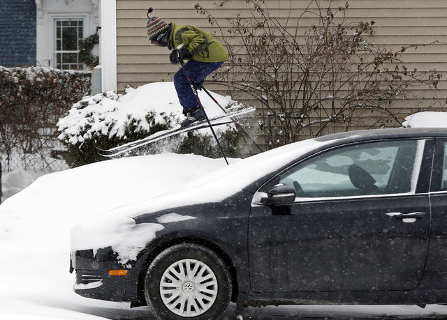 Milo Bloom, 10, skis over a snowbank next to a parked car during a snowstorm, Thursday, Jan. 2, 2014, in Portland, Maine. Strong winds are creating blizzard-like conditions. A wind chill factor of ...