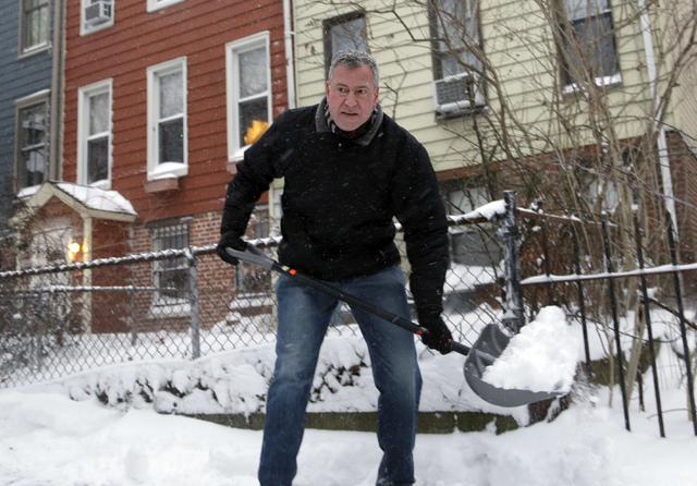 New York City Mayor Bill de Blasio shovels the sidewalk in front of his house in New York, Friday, Jan. 3, 2014. New York City public schools were closed Friday after up to 7 inches of snow fell b ...