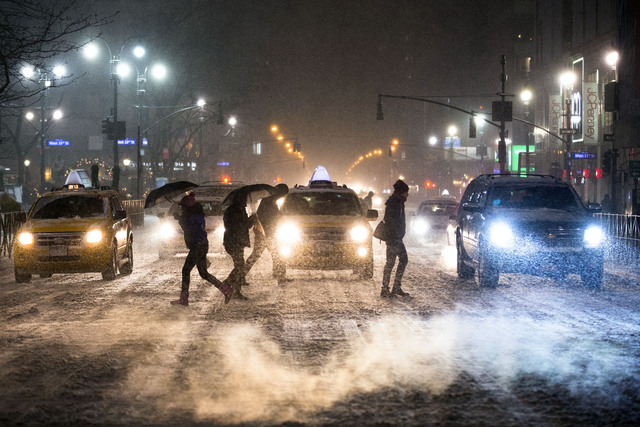 Pedestrians cross 34th Street and 6th Avenue under falling snow in Herald Square, Thursday, Jan. 2, 2014, in New York. The storm is expected to bring snow, stiff winds and punishing cold into the  ...