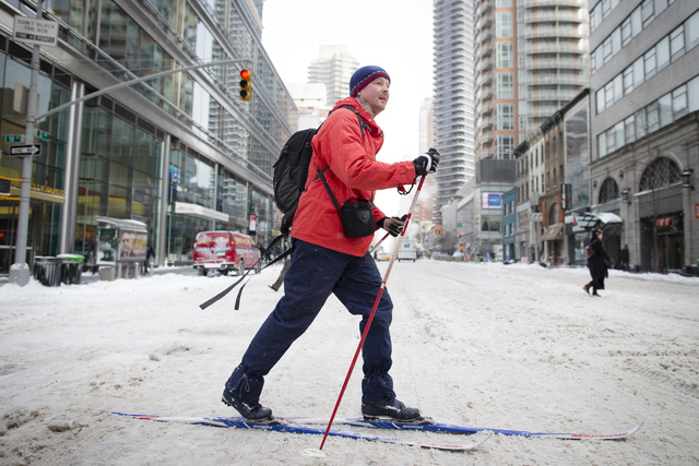 A pedestrian uses his cross-country skies on 58th Street during his morning commute, Friday, Jan. 3, 2014, in New York. New York City public schools were closed Friday after up to 7 inches of snow ...