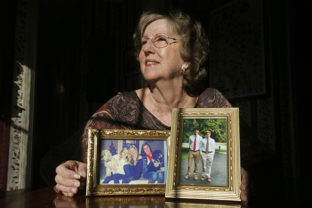 """Penny Trusty, 74,  a retired software designer, shows photographs of her five grandchildren in her home in Rockville, Md. She said she worries about her grandchildren, about the """"lowering of moral ..."""