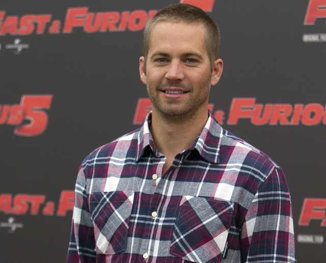 "FILE - In this April 29, 2011 file photo, actor Paul Walker poses during the photo call of the movie ""Fast and Furious 5,"" in Rome.  A coroner's report says the Porsche carrying Walker m ..."