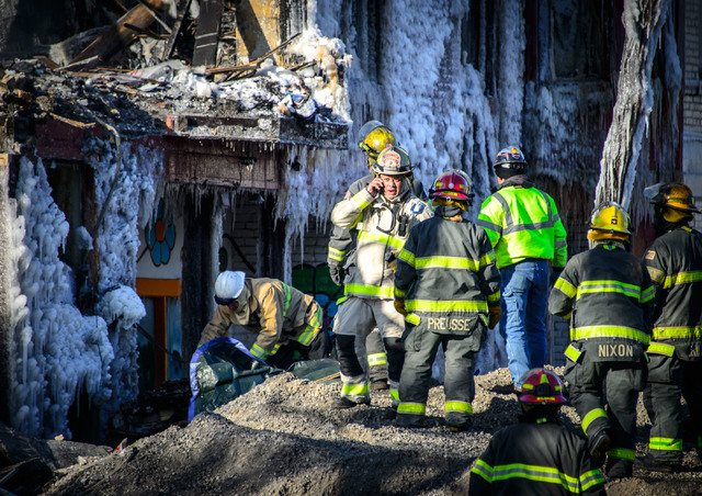 Investigators discover a body of a fire victim, Thursday, Jan. 2, 2014 in Minneapolis.  Authorities said Thursday they have discovered a body in the ruins of a Minneapolis apartment fire, as inves ...