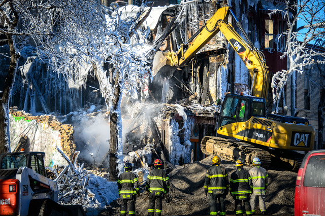 Investigators search for victims, Thursday, Jan. 2, 2014 in Minneapolis.  Authorities said Thursday they have discovered a body in the ruins of a Minneapolis apartment fire, as investigators were  ...