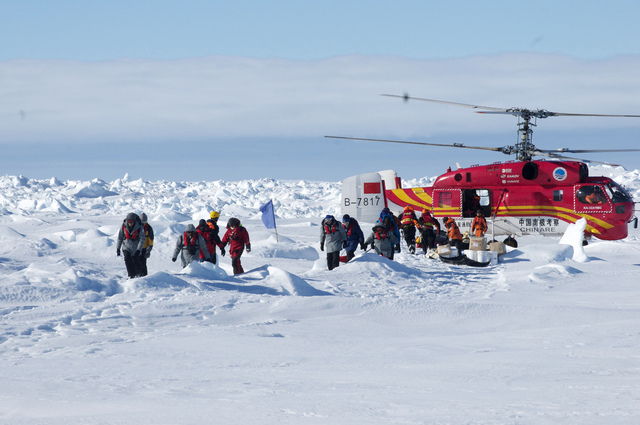 In this image provided by Australasian Antarctic Expedition, passengers trapped for more than a week on the icebound Russian research ship MV Akademik Shokalskiyin are rescued by a Chinese helicop ...
