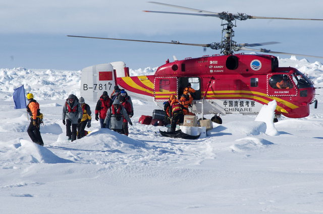In this image provided by Australasian Antarctic Expedition, A Chinese helicopter arrives to rescue some of the 52 passengers trapped for more than a week on the icebound Russian research ship MV  ...