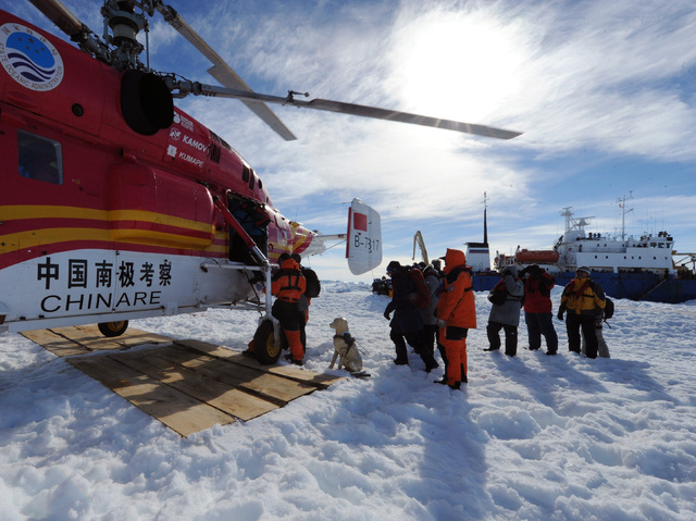 In this photo provided China's official Xinhnua News Agency, passengers from the trapped Russian vessel MV Akademik Shokalskiy, seen at right, prepare to board the Chinese helicopter Xueying 12 in ...