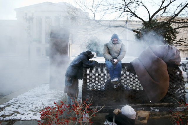 Four homeless men warm themselves on a steam grate by the Federal Trade Commission, blocks from the Capitol, during frigid temperatures in Washington, Saturday, January 4, 2014. A winter storm tha ...