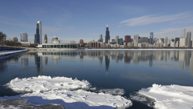 Ice floats on the surface of Lake Michigan Friday, Jan. 3, 2014, in Chicago. Single-digit temperatures are hitting Illinois after the state was blanketed in snow. Meanwhile, residents are bracing  ...