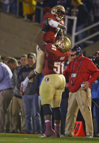 Florida State's Bobby Hart holds up Levonte Whitfield after Whitfield's 100-yard run back of a kickoff during the second half of the NCAA BCS National Championship college football game against Au ...
