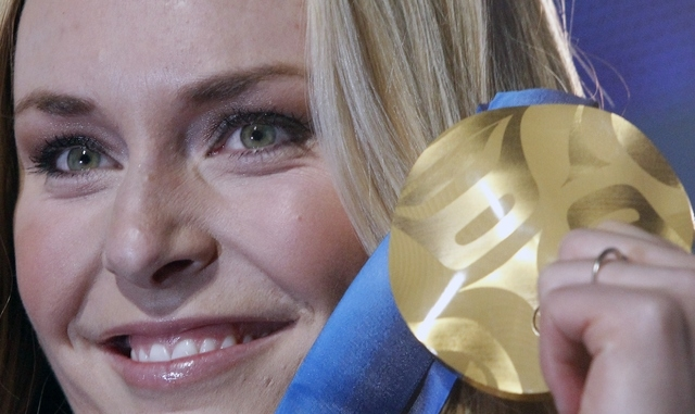 Lindsey Vonn of the United States, shows the gold medal she won in the Women's downhill, during the medal ceremony at the Vancouver 2010 Olympics in Whistler, British Columbia, Canada on Feb. 17,  ...