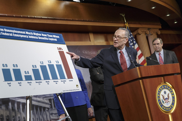 Sen. Charles Schumer, D-N.Y., left, accompanied by Sen. Jeff Merkley, D-Ore., meets with reporters on Capitol Hill in Washington on Tuesday after legislation to renew jobless benefits for the long ...