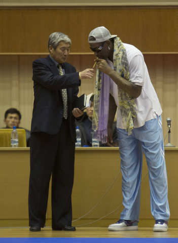 A North Korean official lights a cigar for Dennis Rodman at a basketball arena in Pyongyang, North Korea during a practice session for the US and North Korean team members on Tuesday, Jan. 7, 2014 ...
