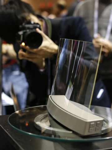 Members of the media photograph a glass speaker called Clio during the International Consumer Electronics Show, Sunday, Jan. 5, 2014, in Las Vegas. The speaker, produced by ClearView Audio uses a  ...