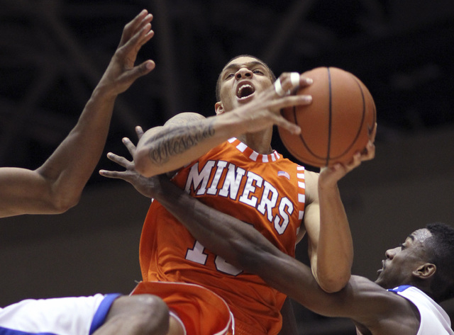 In this March 9, 2013, file photo, UTEP's McKenzie Moore (13) is fouled while defended by SMU's Jordan Dickerson, left, and Ryan Manuel, right, during a game in Dallas. UTEP said Tuesday it has ki ...
