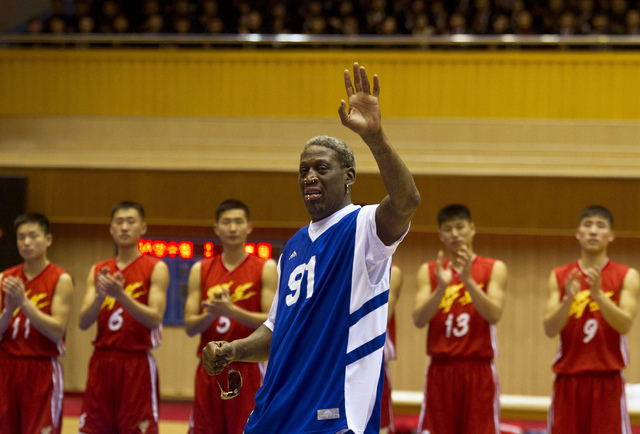 Dennis Rodman waves to North Korean leader Kim Jong Un, seated above in the stands, after singing Happy Birthday to Kim before an exhibition basketball game with U.S. and North Korean players at a ...