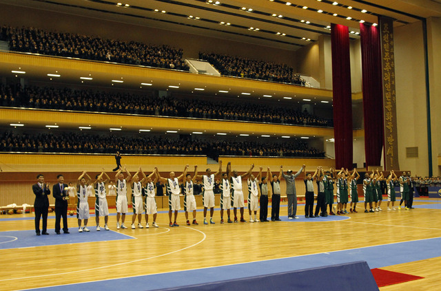 U.S. and North Korean basketball players raise their hands to the crowd after an exhibition game held at an indoor stadium in Pyongyang, North Korea on Wednesday, Jan. 8, 2014. Former NBA star Den ...