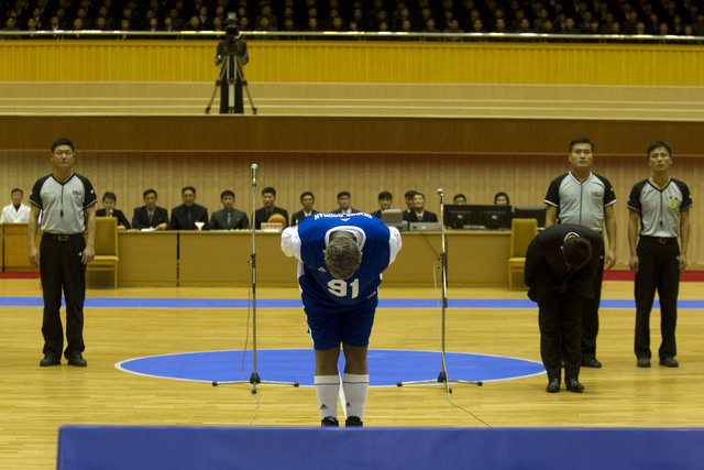 Dennis Rodman bows to North Korean leader Kim Jong Un, seated above in the stands, before an exhibition basketball game with U.S. and North Korean players at an indoor stadium in Pyongyang, North  ...