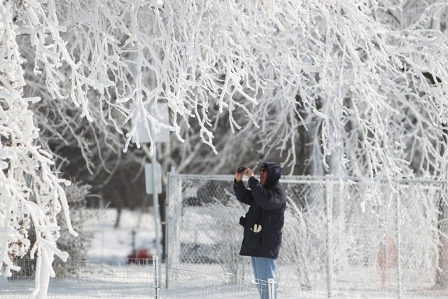 A tourist takes a photograph of the winter wonderland created by freezing mist from Niagara Falls in Niagara Falls State Park, Niagara Falls, N.Y. on Thursday, Jan. 9, 2014.  Niagara Falls hasn't  ...